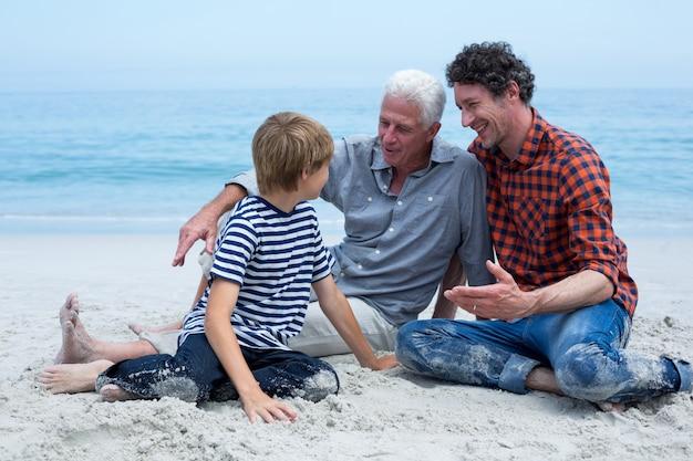 Rodzina wielopokoleniowa odpoczywa na brzegu morza Premium Zdjęcia