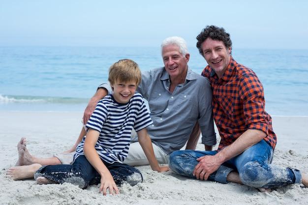 Rodzina wielopokoleniowa, uśmiechnięta podczas relaksu na brzegu morza Premium Zdjęcia