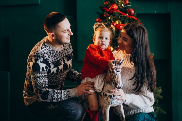 Rodzina z małą córeczką przy choince bawi się z drewnianym kucykiem Darmowe Zdjęcia