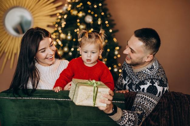Rodzina Z Małą Córeczką Siedzącą Przy Choince I Rozpakowaniu Pudełko Darmowe Zdjęcia