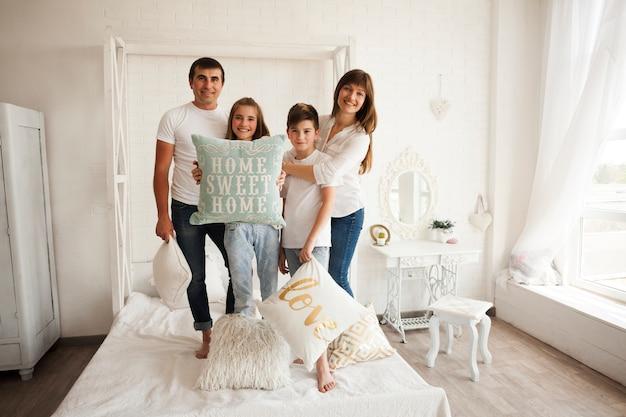 Rodzinna pozycja na łóżku z mienia domowym słodkim domowym tekstem na poduszce Darmowe Zdjęcia