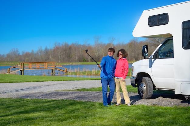 Rodzinne Wakacje, Podróż Samochodem Rv, Szczęśliwa Para Robi Selfie Przed Kamperem Na Wakacyjnej Wycieczce Samochodem Kempingowym Premium Zdjęcia
