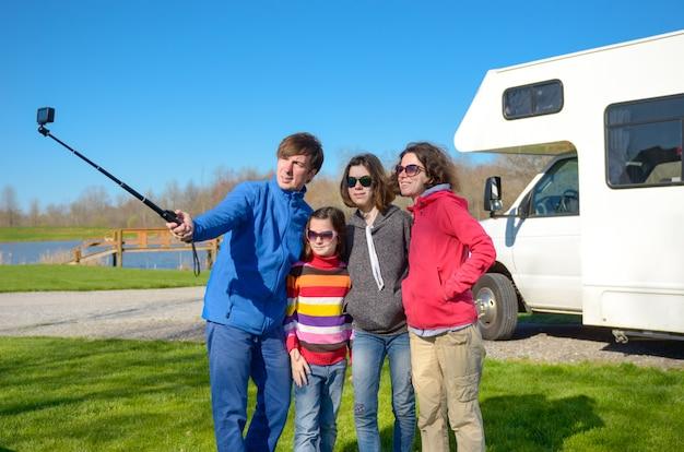 Rodzinne Wakacje, Podróż Samochodem Rv Z Dziećmi, Szczęśliwi Rodzice Z Dziećmi Bawią Się I Robią Selfie Na Wakacyjnej Podróży Samochodem Kempingowym Premium Zdjęcia