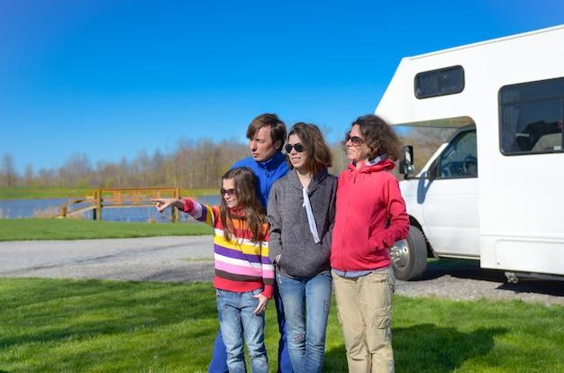 Rodzinne Wakacje, Podróż Samochodem Rv Z Dziećmi, Szczęśliwi Rodzice Z Dziećmi Bawią Się Podczas Wakacyjnej Podróży Samochodem Kempingowym, Na Zewnątrz Kampera Premium Zdjęcia
