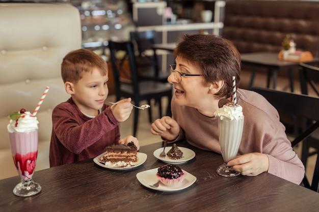 Rodzinny Wypoczynek I Rozrywka. Szczęśliwa Babcia Z Krótkimi Włosami, Okularami I Wnukiem Odpoczywa W Kawiarni. Jedzą Ciasta Z Koktajlami Mlecznymi I Traktują Się Nawzajem Premium Zdjęcia