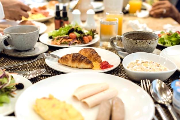 Rogaliki To Składnik śniadania. śniadanie Na Stole Z Kawą, Sokiem Pomarańczowym, Owocami, Sałatką, Jajkiem, Bekonem, Rogalikami, Marmoladą, Mlekiem I Wodą Premium Zdjęcia