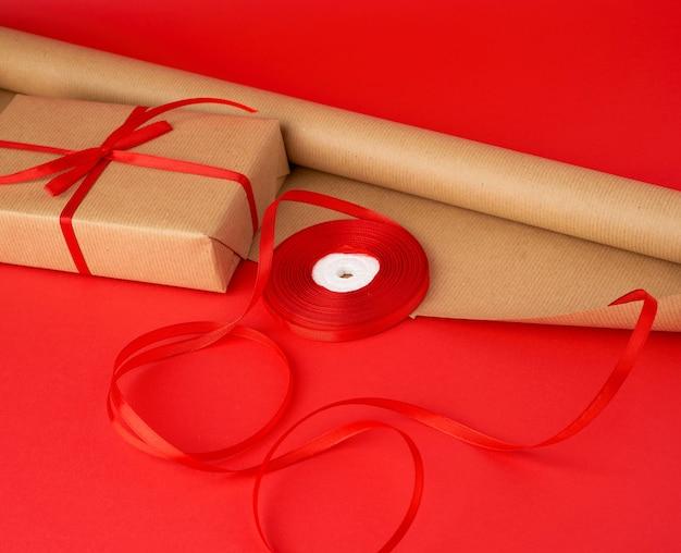 Rolka Brązowego Papieru Do Pakowania, Rolka Czerwonej Wstążki I Owinięty Prezent W Brązowy Papier Pakowy Na Czerwonym Premium Zdjęcia
