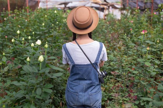 Rolnicza kobieta trzyma pastylkę w ogródzie różanym. Darmowe Zdjęcia