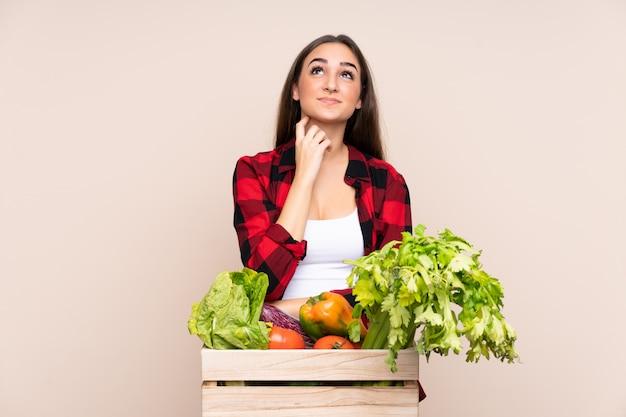 Rolnik Ze świeżo Zebranych Warzyw W Pudełku Na Beżowej ścianie Myślący Pomysł Premium Zdjęcia