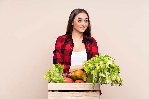 Rolnik Ze świeżo Zebranych Warzyw W Pudełku Na Beżowym Myśleniu Pomysł Premium Zdjęcia