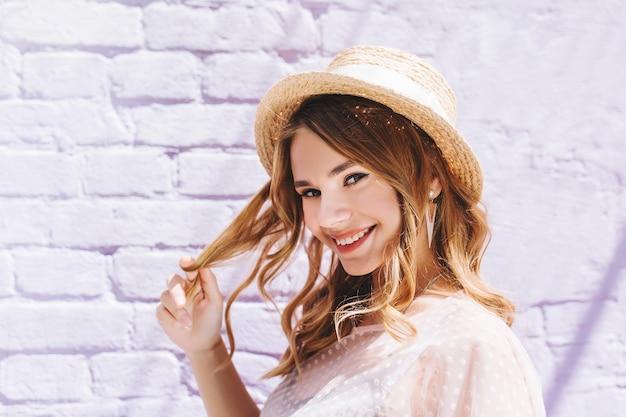 Romantyczna Blondynka O Pięknych Oczach Szczęśliwa, Uśmiechnięta I Dotykająca Jej Jasne Włosy Darmowe Zdjęcia
