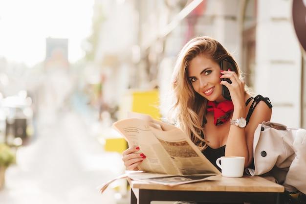 Romantyczna Dama Z Gazetą Pozowanie W Kawiarni Z ładnym Uśmiechem, Z Tłumem W Tle Darmowe Zdjęcia