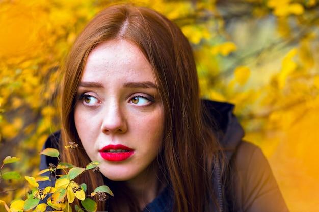 Romantyczna Dziewczyna Z Lśniącymi Prostymi Włosami Odwracająca Wzrok, Chowająca Się Za żółtymi Liśćmi. Szczegół Odkryty Portret Samotnej Brunetki Modelki Pozowanie W Parku Jesienią. Darmowe Zdjęcia