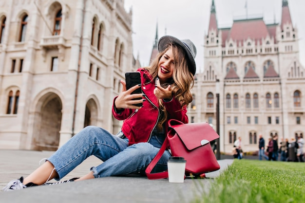 Romantyczna Kobieta W Dżinsach Retro Siedzi Na Ziemi I Rozmawia Przy Użyciu Połączenia Wideo Darmowe Zdjęcia