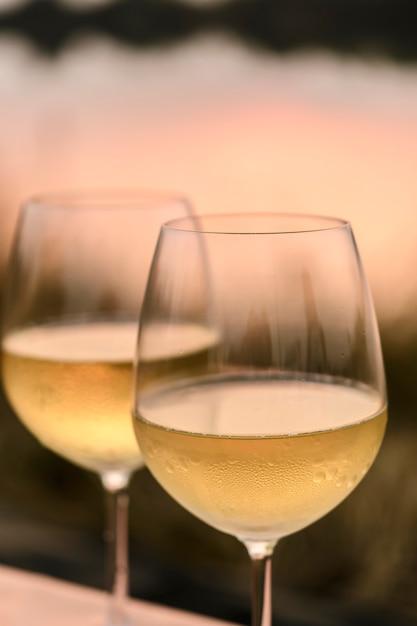 Romantyczna kolacja latem na plaży o zachodzie słońca z dwiema szklankami białego wina Premium Zdjęcia