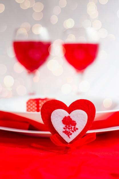 Romantyczna Kolacja Na Walentynki. Serce Z Widelcem I Białymi Talerzami Na Jasnym Tle Premium Zdjęcia