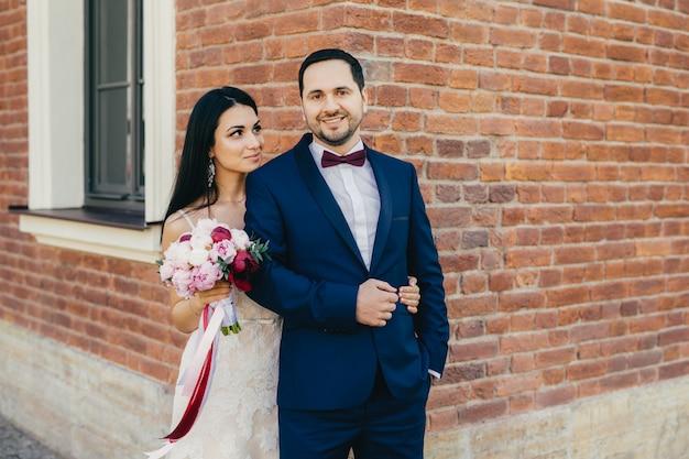 Romantyczna młoda urocza para małżeńska pozuje do robienia zdjęć, ma szczęśliwe zachwycające miny Premium Zdjęcia