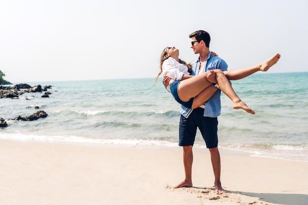 Romantyczna Para Młodych Kochanków Relaks Razem Na Tropikalnej Plaży. Mężczyzna Przytulanie Z Kobietą I Cieszyć Się życiem. Wakacje Letnie Premium Zdjęcia