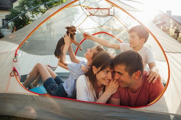 Romantyczna para patrząc na siebie, podczas gdy ich dzieci bawiące się z psem w namiocie Darmowe Zdjęcia