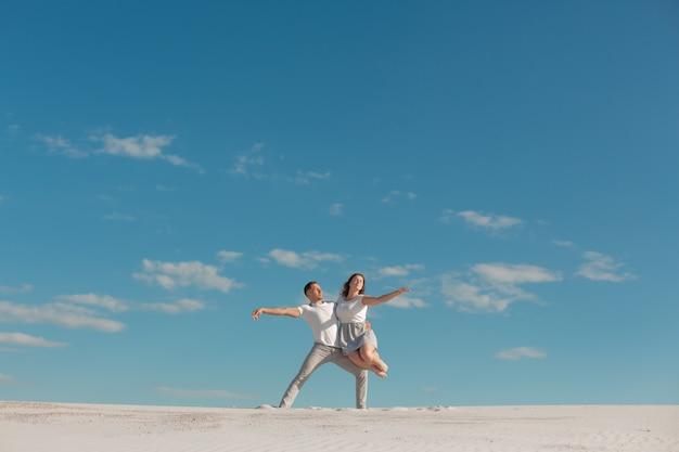 Romantyczna para taniec w piasek pustyni w błękitne niebo Premium Zdjęcia