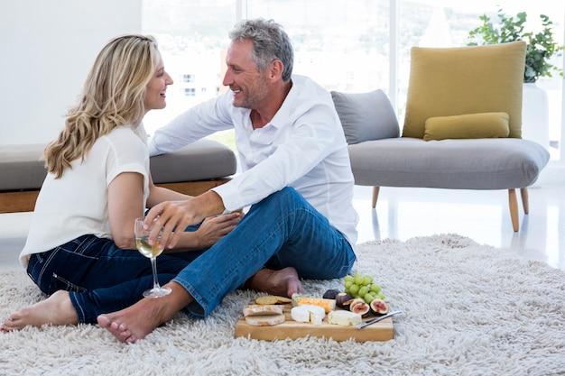 Romantyczna Para Z Białym Winem I Jedzeniem Siedząc Na Dywanie Premium Zdjęcia