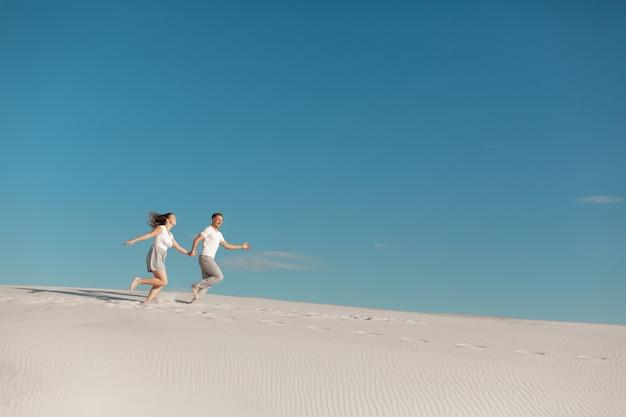 Romantyczna para zakochanych działa na białym piasku na pustyni. Premium Zdjęcia
