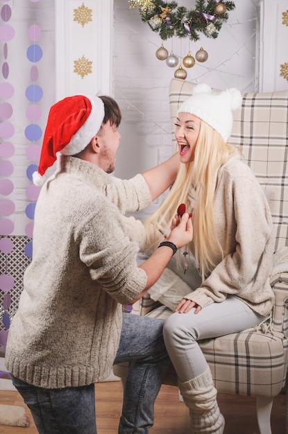 Romantyczna propozycja zaręczynowa (małżeństwo) w wigilię, szczęśliwi młodzi zakochani - koncepcja miłości i zaręczyn Premium Zdjęcia