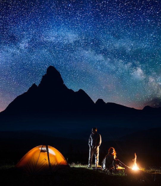 Romantyczni para turyści w jego obozie przy nocą blisko ogniska i namiotu przeciw wysokiemu góry tłu i gwiaździstemu niebu Premium Zdjęcia