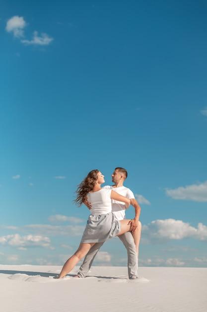 Romantyczny para taniec w piasek pustyni przy niebieskiego nieba tłem Premium Zdjęcia