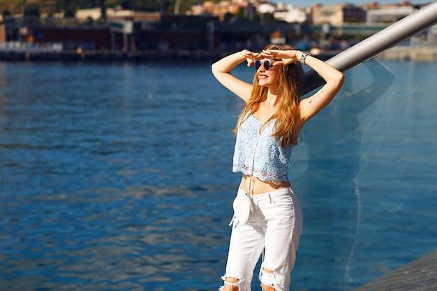 Romantyczny Portret Zmysłowej Blondynki Z Widokiem Na Morze, Modny Letni Strój, Pastelowe Kolory, Samotna Podróż, Wakacje, Biały Dżins, Okulary Przeciwsłoneczne. Darmowe Zdjęcia