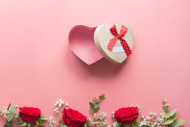 Romantyczny różowy tło z czerwonych róż kwiaty i pudełko w kształcie serca Premium Zdjęcia