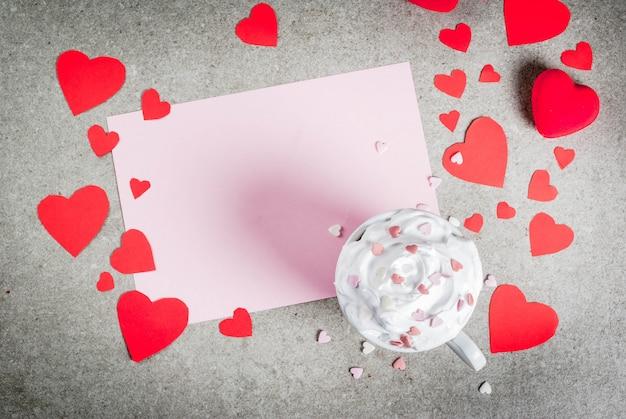 Romantyczny tło walentynki kamienny stół z czystym papierem na gratulacje z listu gorąca czekolada z bitą śmietaną i słodkie serca ozdobione papierowymi czerwonymi sercami Premium Zdjęcia