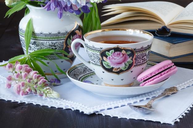 Romantyczny Tło Z Filiżanką Kwiatów Herbaty I Otwartą Książkę Na Białym Stole Premium Zdjęcia