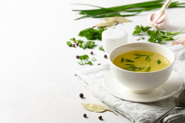 Rosół Z Kurczaka Z Zieloną Cebulą W Białej Misce Na Białym Stole. Skopiuj Miejsce Premium Zdjęcia