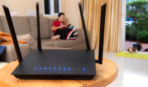 Router bezprzewodowy i kobieta za pomocą telefonu w salonie w domu Premium Zdjęcia