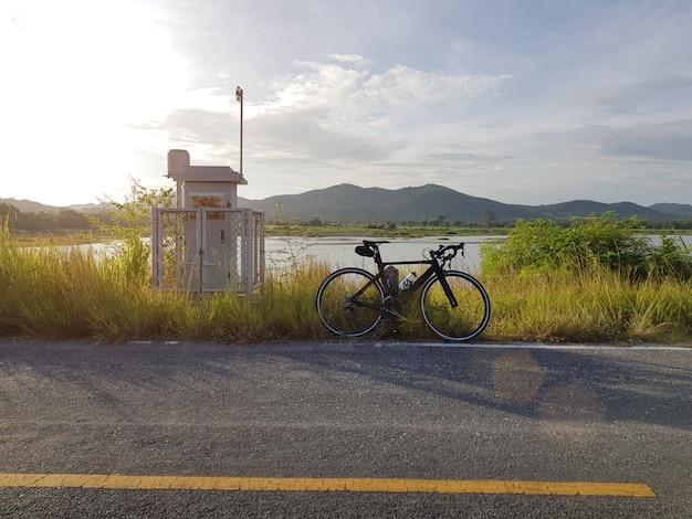 Rower parkujący obok otwartej drogi z niebieskim niebem Premium Zdjęcia
