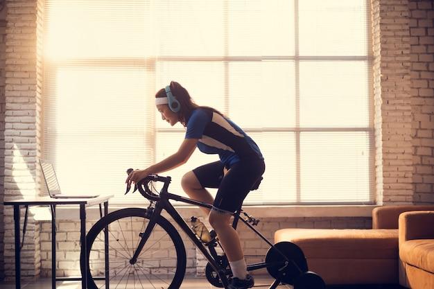 Rowerzysta Azjatyckie Kobiety. ćwiczy W Domu, Jeździ Rowerem Na Trenerze I Gra W Gry Rowerowe Online Premium Zdjęcia