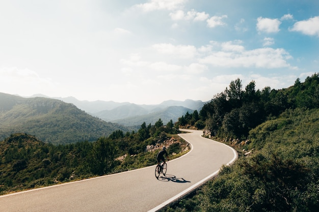 Rowerzysta, Jazda Na Rowerze O Zachodzie Słońca W Górskiej Jezdni Darmowe Zdjęcia