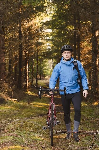 Rowerzysta W Niebieskim Płaszczu I Kasku W Parku Z Wysokimi Drzewami Darmowe Zdjęcia