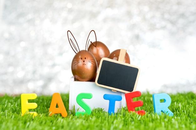 Różany Złocisty Easter Jajko W Drewnianym Białym Pudełku I Pusta Blackboard Klamerka Na Zielonej Trawy Polu Premium Zdjęcia