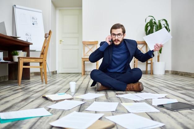 Rozbawiony Biznesmen Pracuje Na Podłoga W Biurze Premium Zdjęcia