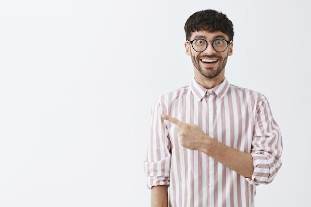 Rozbawiony Stylowy Brodaty Facet Pozujący Przy Białej ścianie W Okularach Darmowe Zdjęcia