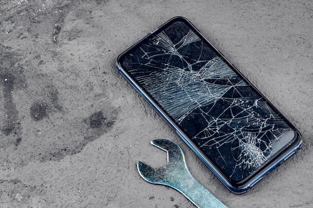 Rozbity Smartfon Z Narzędziami Do Naprawy Na Szaro Premium Zdjęcia