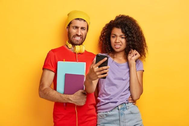 Rozczarowani Wieloetniczni Przyjaciele Patrzą Z Niechęcią Na Smartfony, Oglądają Nieprzyjemne Filmy Online Darmowe Zdjęcia