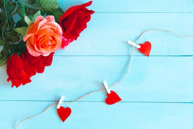 Róże Na Niebieskim Tle I Serca Złapane Sznurkiem. Walentynki Tło Premium Zdjęcia