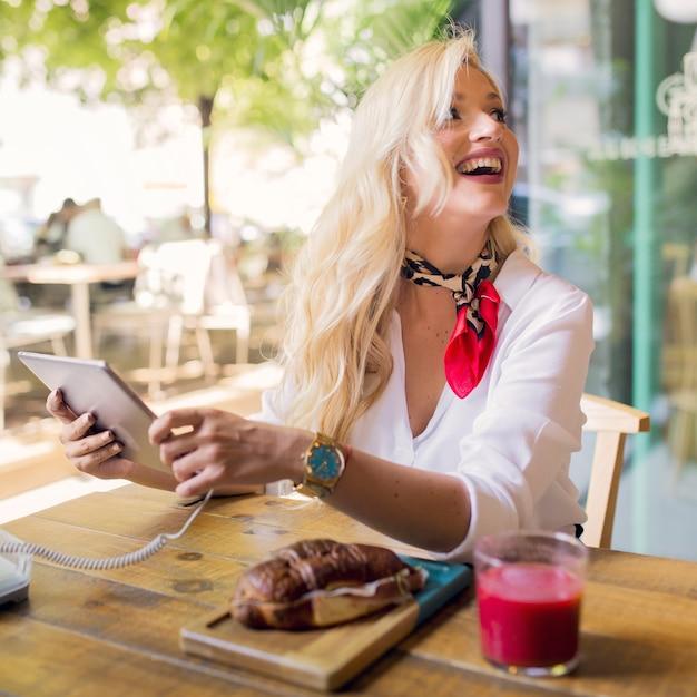 Roześmiana blondynki młoda kobieta dołącza kabel na cyfrowej pastylce w caf� Darmowe Zdjęcia