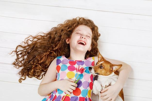 Roześmiana dziewczyna obejmuje psa kłaść na ciepłej drewnianej podłoga. Premium Zdjęcia