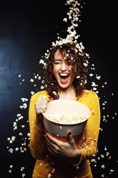 Roześmiana Młoda Kobieta Zostaje Pod Tandetnym Popcorn Prysznic W Kinie Darmowe Zdjęcia