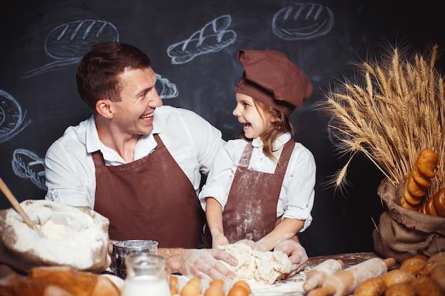 Roześmiany mężczyzna z córką robi chlebowi Premium Zdjęcia