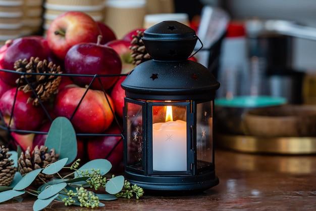 Rozjarzony świeczka Lampion I Kosz Jabłka Na Stole W Bożych Narodzeniach Wprowadzać Na Rynek W Ryskim, Latvia Premium Zdjęcia